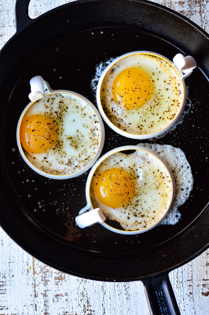 Three sunny-side up eggs in egg rings in a cast iron skillet