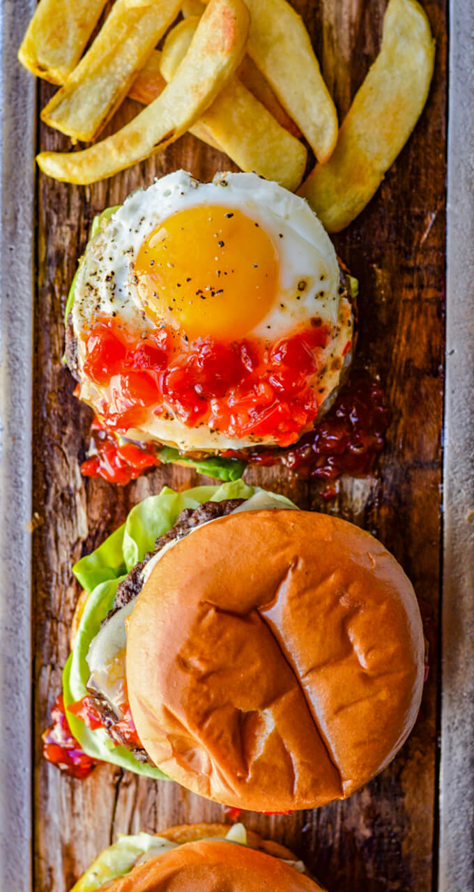 Bison burgers on a wooden board, one without a top bun showing a sunny-side up egg and peppadew jam with french fries