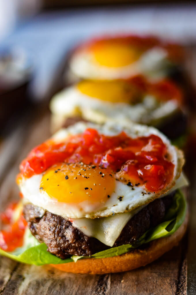 A front shot of a bison burger without the top bun, a sunny-side up egg with peppadew jam, with two burgers blurred in the background