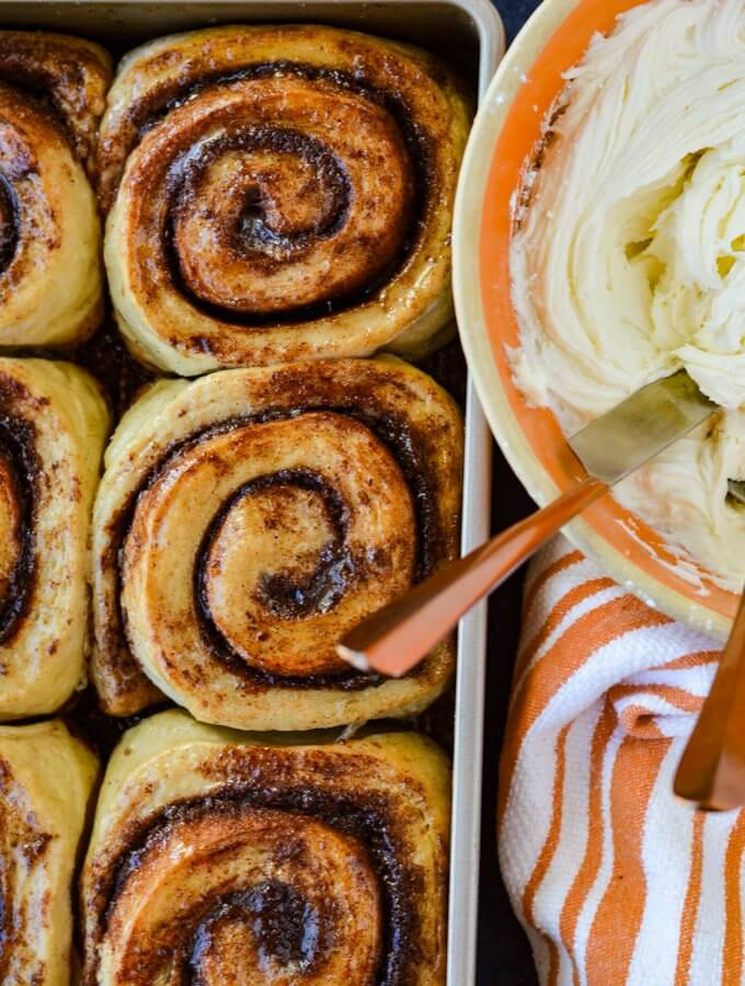 Baked cinnamon rolls in a pan with a bowl of icing beside it and an orange and white striped towel.
