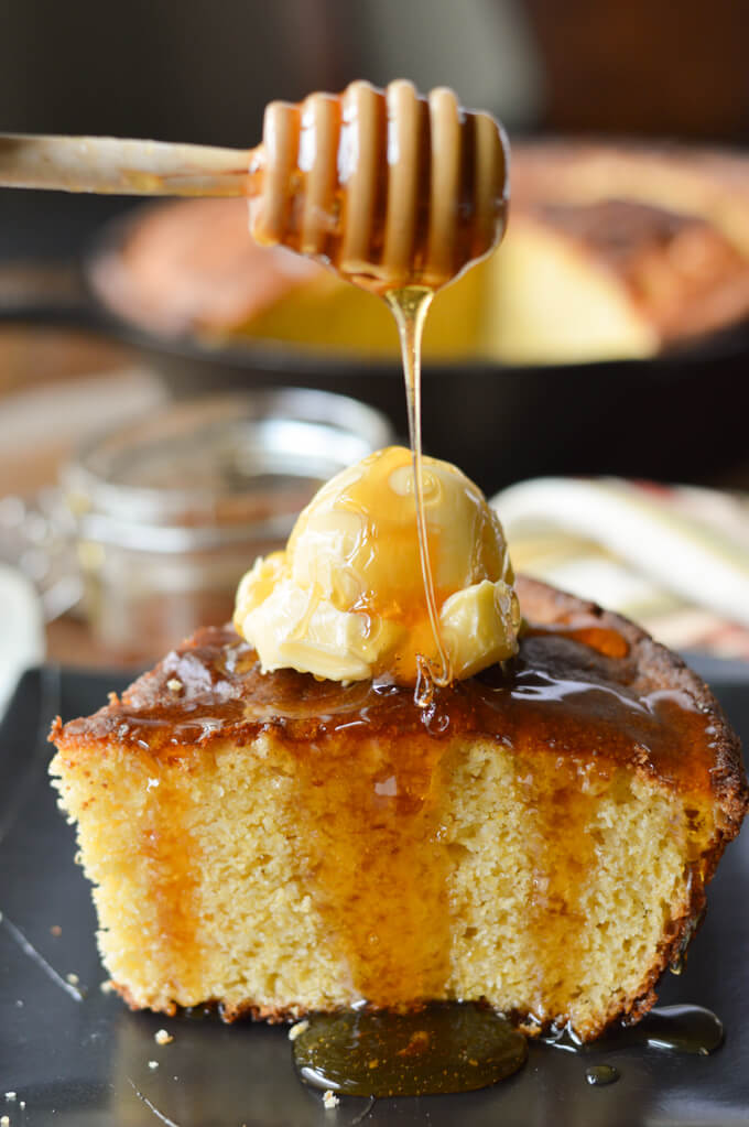 A piece of gold brown cornbread with a dollop of butter on top and honey dripping on top.