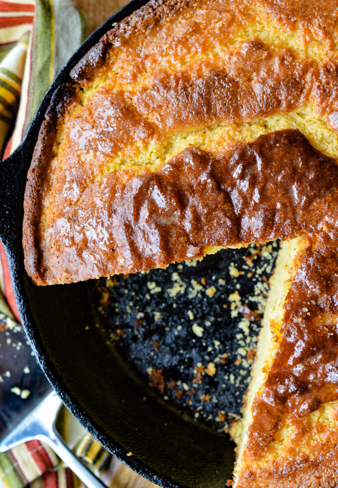 A golden browned pan of cornbread with a slice taken out.
