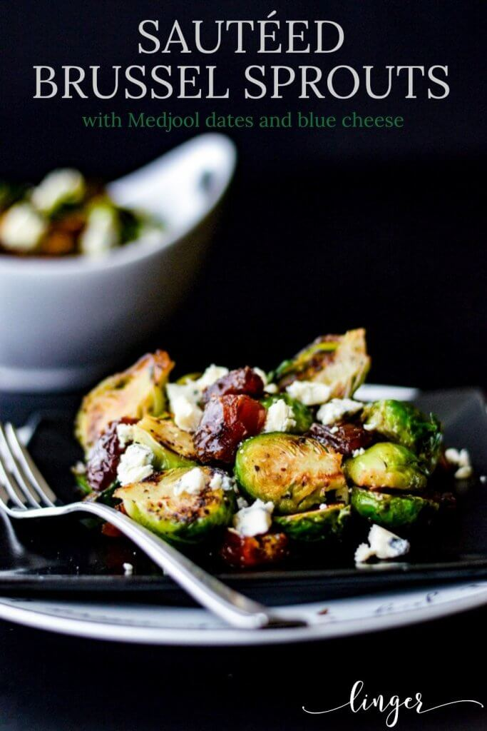 A black plate with pan roasted brussel sprouts, blue cheese and dates. A white bowl holding the same is in the background.