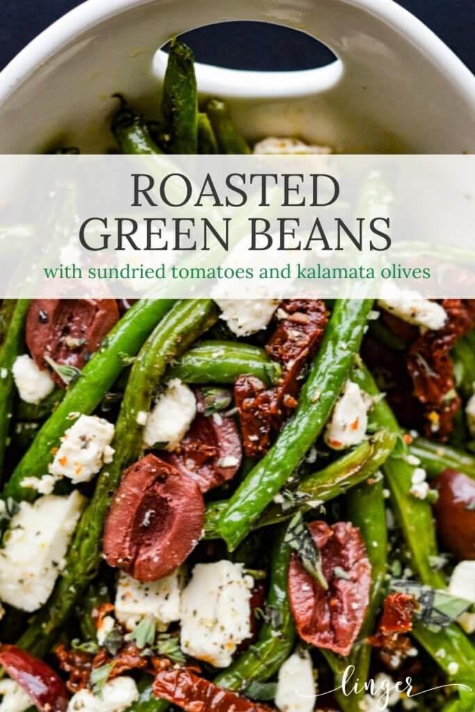 A white bowl of fresh roasted green beans, sundried tomatoes, kalamata olives and feta cheese.