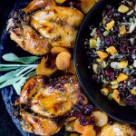 Four roasted cornish hens with an apricot glaze sit on top of a wild rice stuffing on black plates. A black bowl of wild rice stuffing sits next to it.