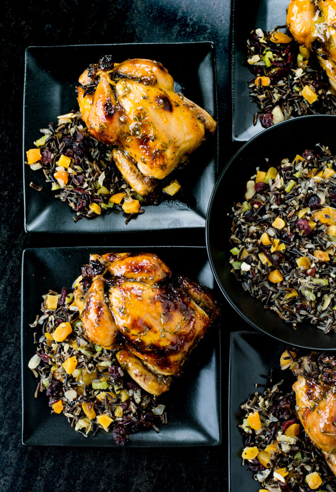 Two roasted cornish hens with an apricot glaze sit on top of a wild rice stuffing on black plates. A black bowl of wild rice stuffing sits next to it.