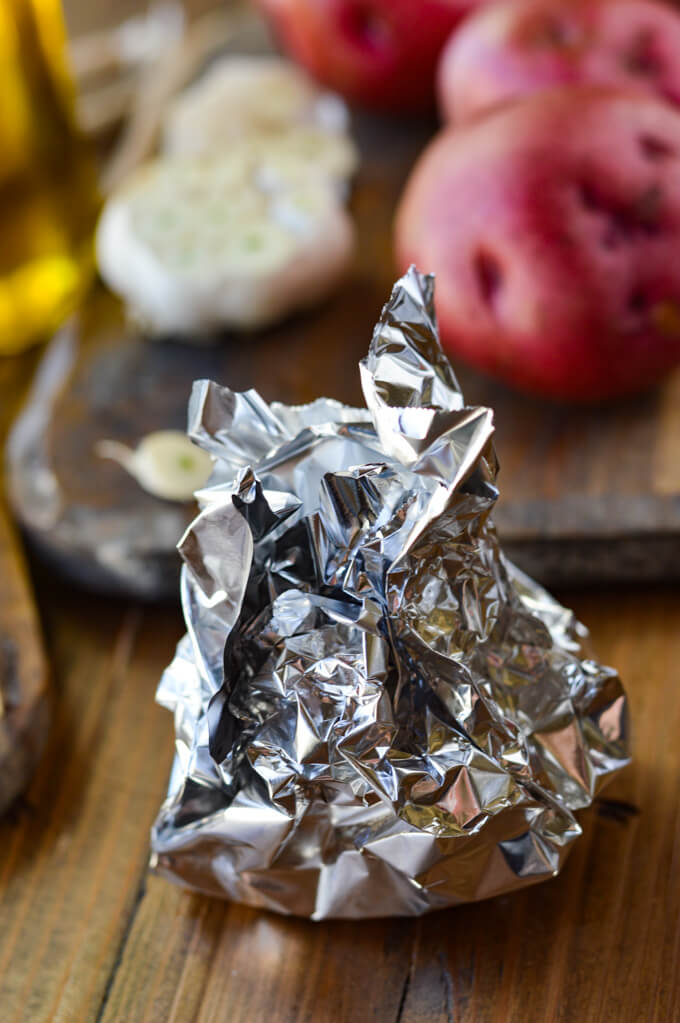 A garlic bulb wrapped up in a piece of foil with red potatoes and a cut garlic bulb in the background.