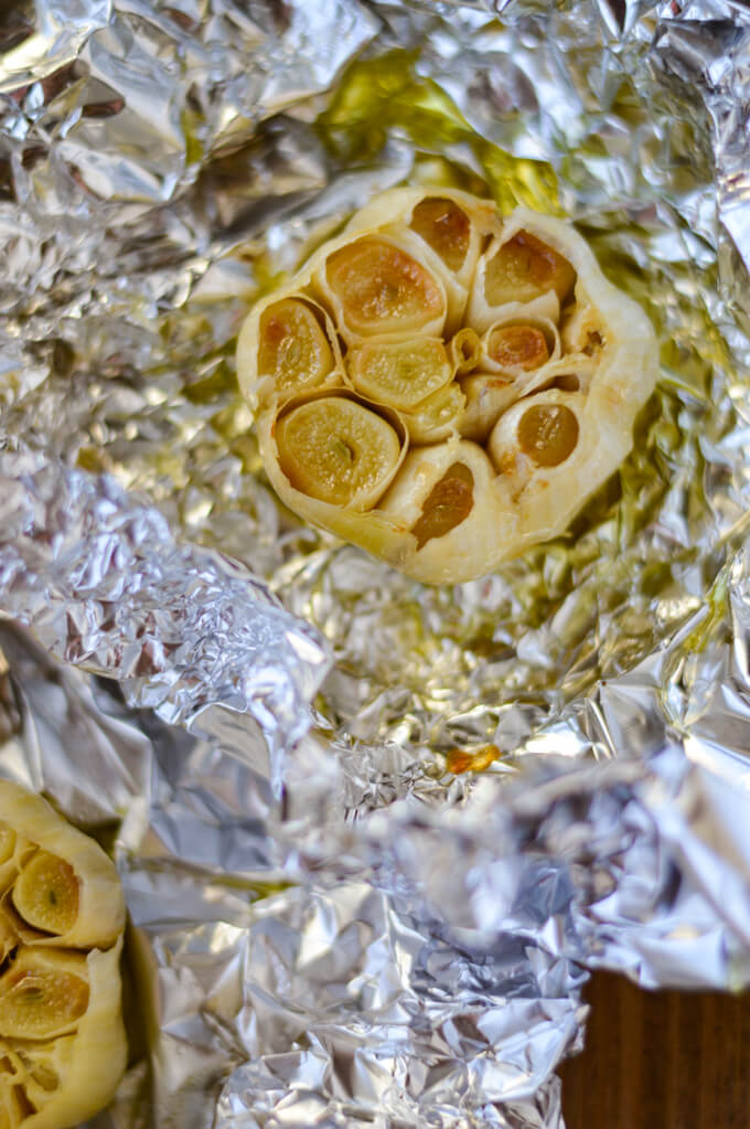 A roasted garlic bulb with its top off sitting in a piece of foil with olive oil on it.
