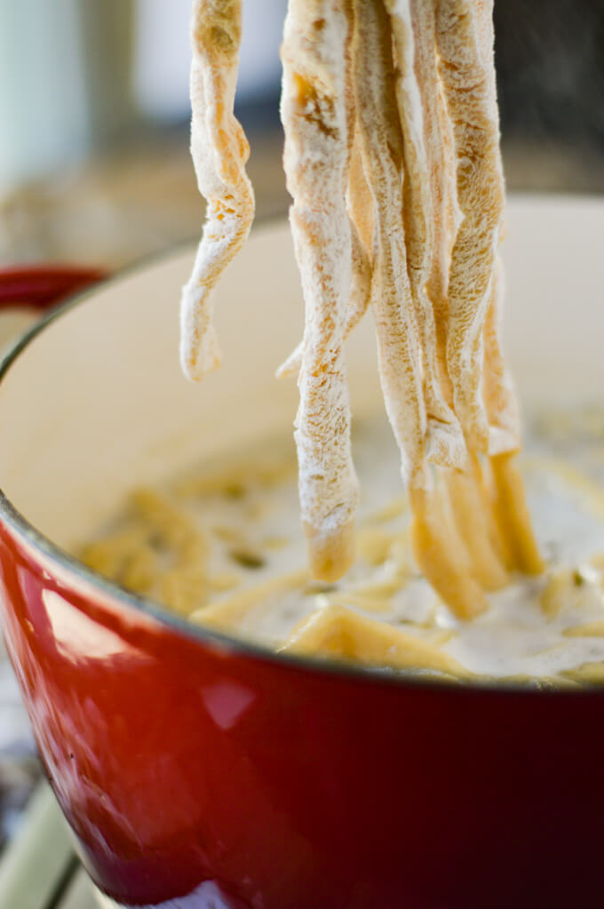 Egg noodles being lowered into a pot of boiling chicken broth for chicken and noodles.