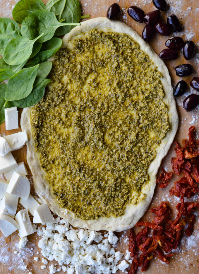 A rolled out pizza dough with pesto sauce and spinach, feta and mozzarella cheese, kalamata olives and sundried tomatoes all around the dough.