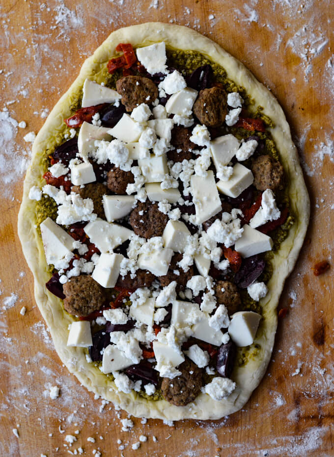 An uncooked mediterranean pizza with lamb, kalamata olives, sun-dried tomatoes and mozzarella and feta cheese as the toppings.