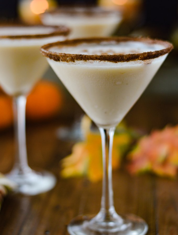 Three pumpkin spice martinis with spiced sugar on the rims and fall decorations around.