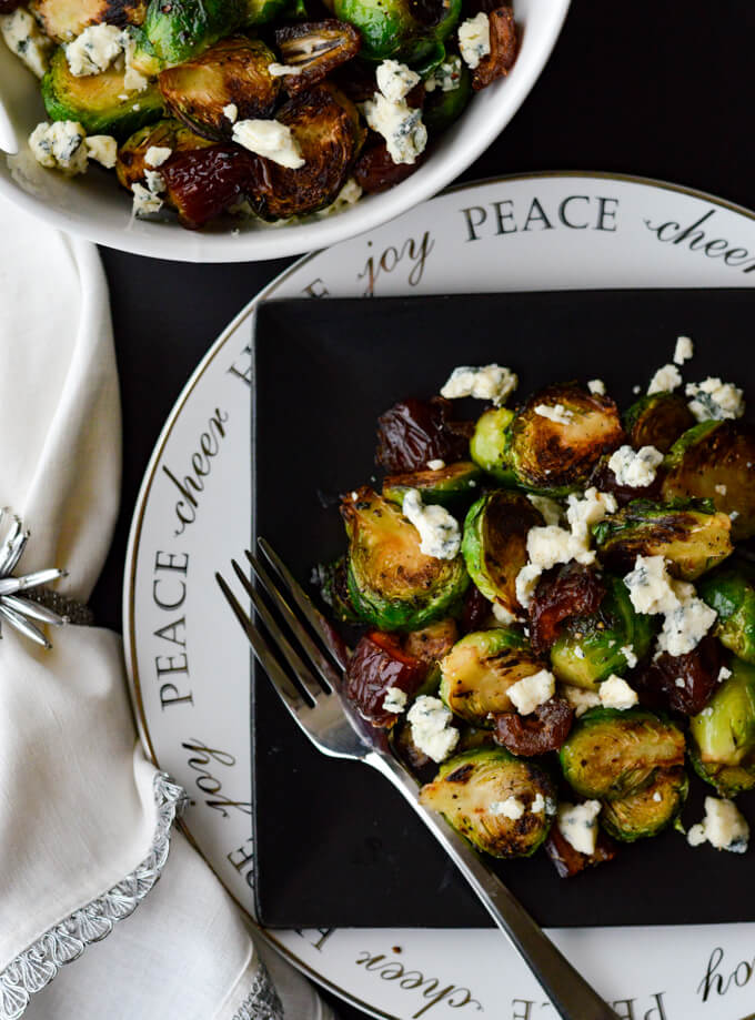Pan Roasted Brussel Sprouts with blue cheese and medjool dates on a black plate that is sitting on a white plate with a white napkin beside it.