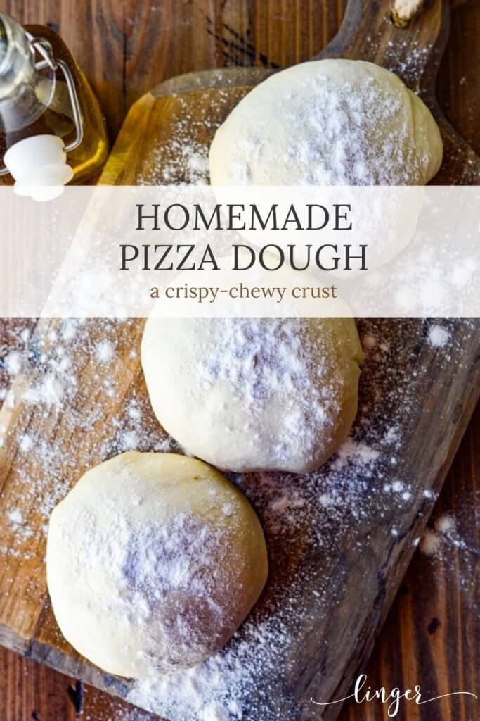 Three balls of pizza dough rest on a floured wooden board with olive oil in the background.