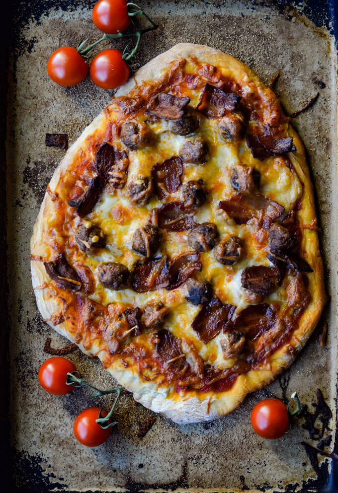 A cooked all-meat pizza on a pizza stone with cherry tomatoes scatter around.