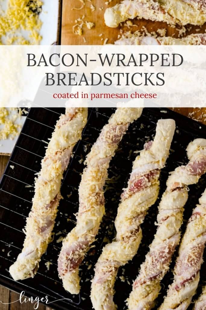 Bacon Wrapped Breadsticks are on a cookie sheet with a wire rack over it. A platter of shredded cheese and a few more breadsticks sit next to the pan.