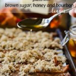 A cookie sheet with cooked bacon slices and sprinkled with brown sugar. A spoonful of honey and bourbon is being poured onto the slices. A jar of honey, and a bottle of bourbon with an orange and red napkin lays beside the pan.