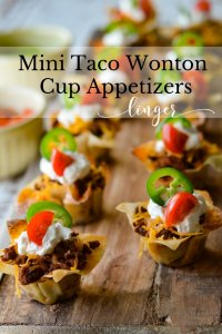 Mini Taco Wonton Cups with sour cream, cherry tomato and jalapeno slices. All of these appetizers are sitting on a wooden board with a cup of tomatoes sitting next to it.