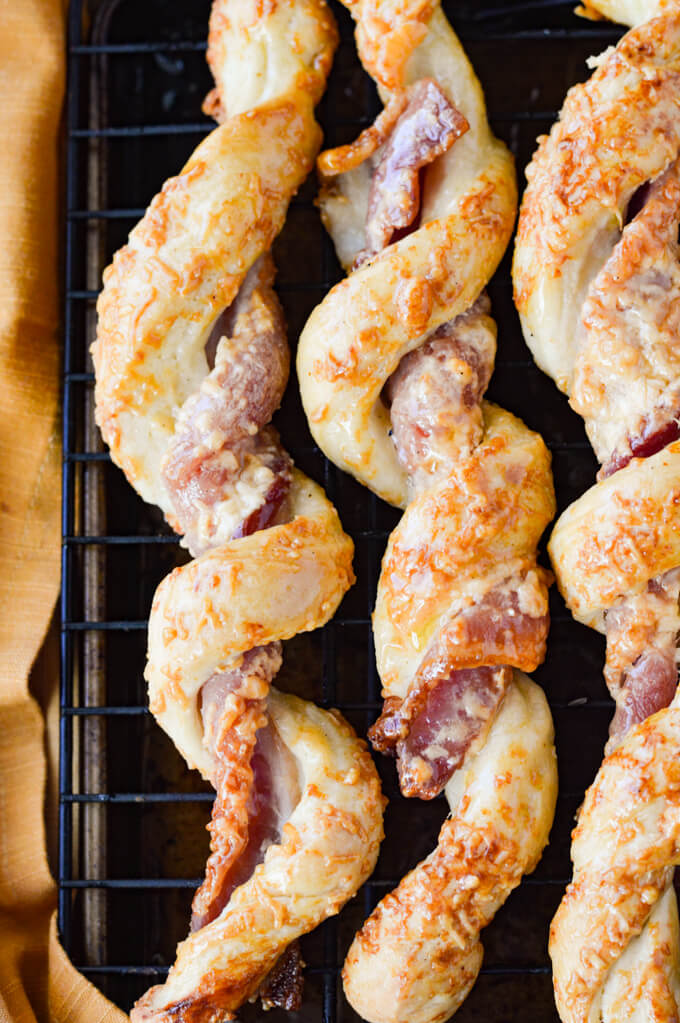 A closeup of baked bacon wrapped breadsticks on a wire rack.