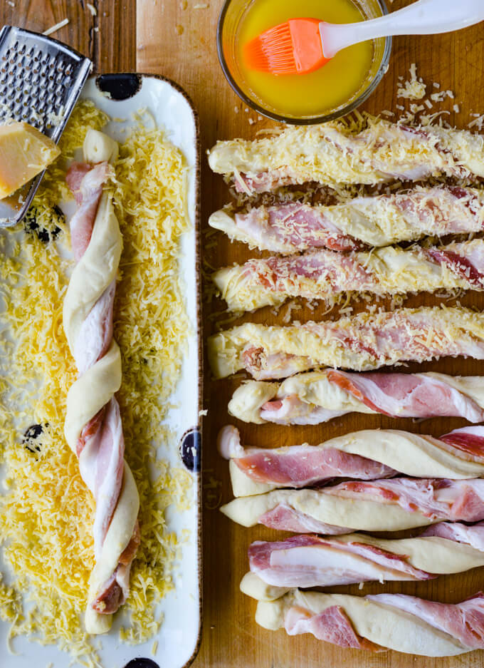 A line of bacon wrapped breadsticks. Some are covered in shredded cheese and one is in a platter filled with schredded cheese. A bowl of butter sits next to it.