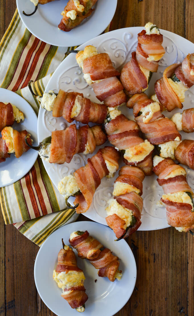 A plateful of cooked cheese filled bacon wrapped jalapeño poppers. Three small plates hold two poppers each with a striped napkin laying under them.