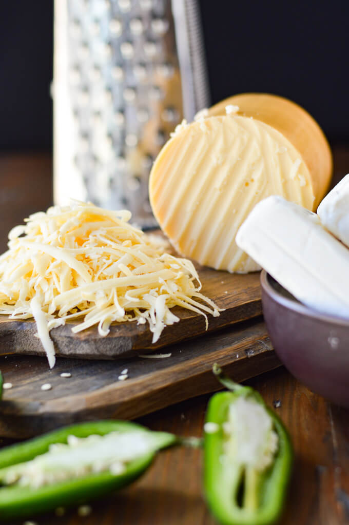 A round wedge of gouda cheese and shredded cheese on a wooden board with a cheese grater in the background. There's a bowl of cream cheese and halved fresh halapeños in the forefront.