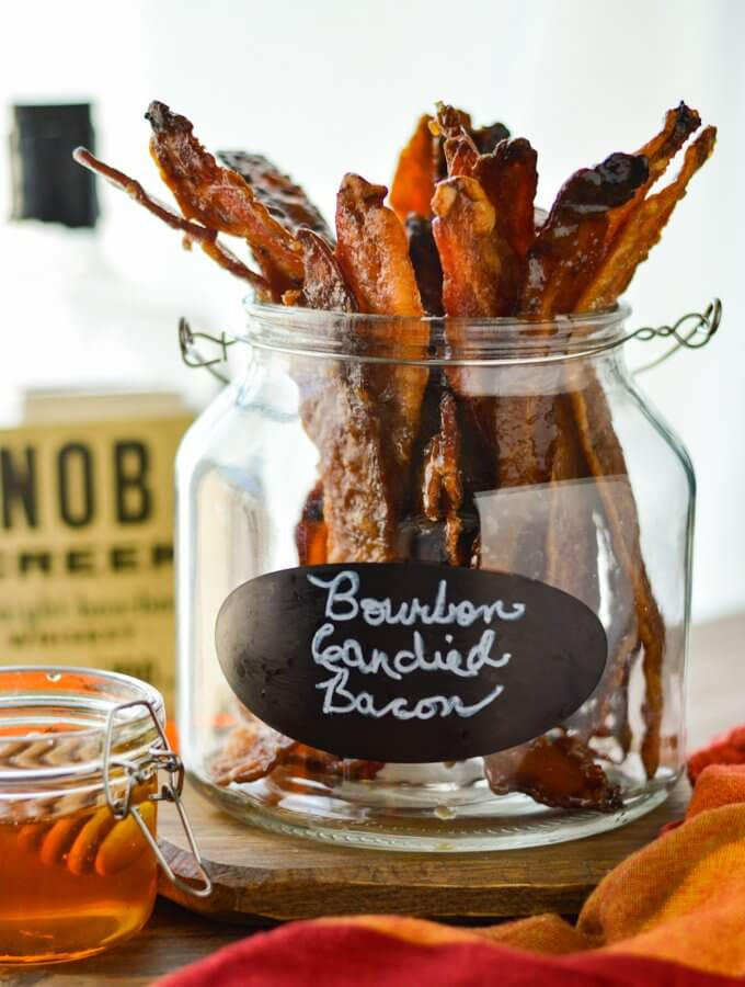 A jar of Bourbon Candied Bacon with bourbon in the background and honey beside the jar. There's a label with the words Bourbon Candied Bacon on it.