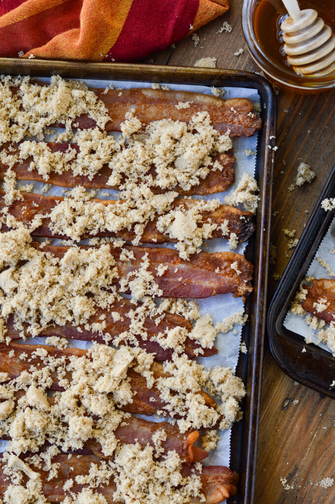 Slices of cooked bacon on a cookie sheet lined with parchment paper. Brown sugar is sprinkled all over the bacon. There's a bowl of honey and an orange and red napkin next to it.