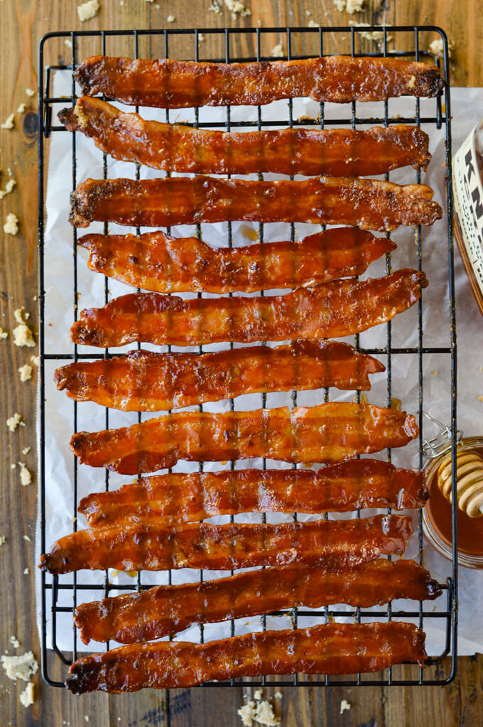 Candied Bacon cooling on a wire rack with parchment paper underneath it.