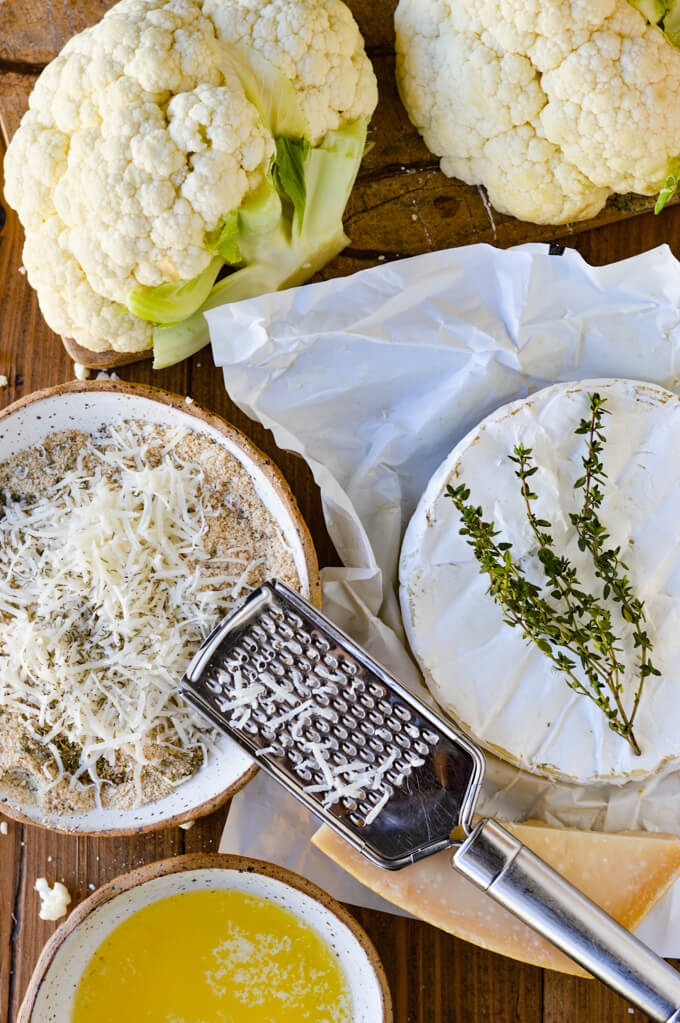 A bowl of breadcrumbs with herbs and parmesan cheese. A round of brie cheese sitting on the white wrapper with sprigs of thyme on top. A cheese grater and a chunk of parmesan cheese, a bowl of melted butter and cauliflower halves sit next to the cheeses.