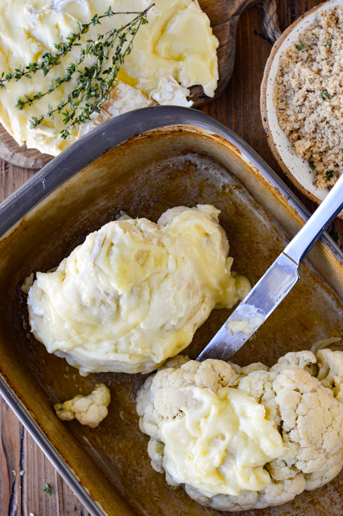 Two cauliflower halves sit in a shallow stoneware pan with a butter knife that is spreading brie cheese on them. A bowl of breadcrumbs and a round of brie with sprigs of thyme on it sits next to the pan.