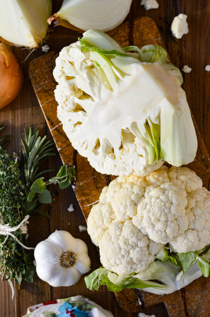 A wooden board with two halves of a cauliflower on it with garlic, onion quarters and a bunch of fresh herbs bundled together next to the cauliflower.