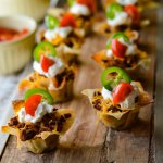 Mini Taco Wonton Cups with sour cream, cherry tomato and jalapeno slices. All of these appetizers are sitting on a wooden board with a cup of tomatoes and jalapenos sitting next to it.