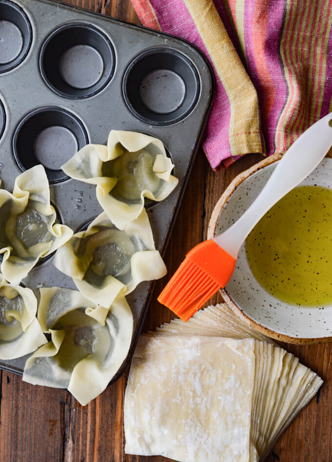Wontons in mini muffin tin with olive oil and brush. A pink napkin sits next to them.