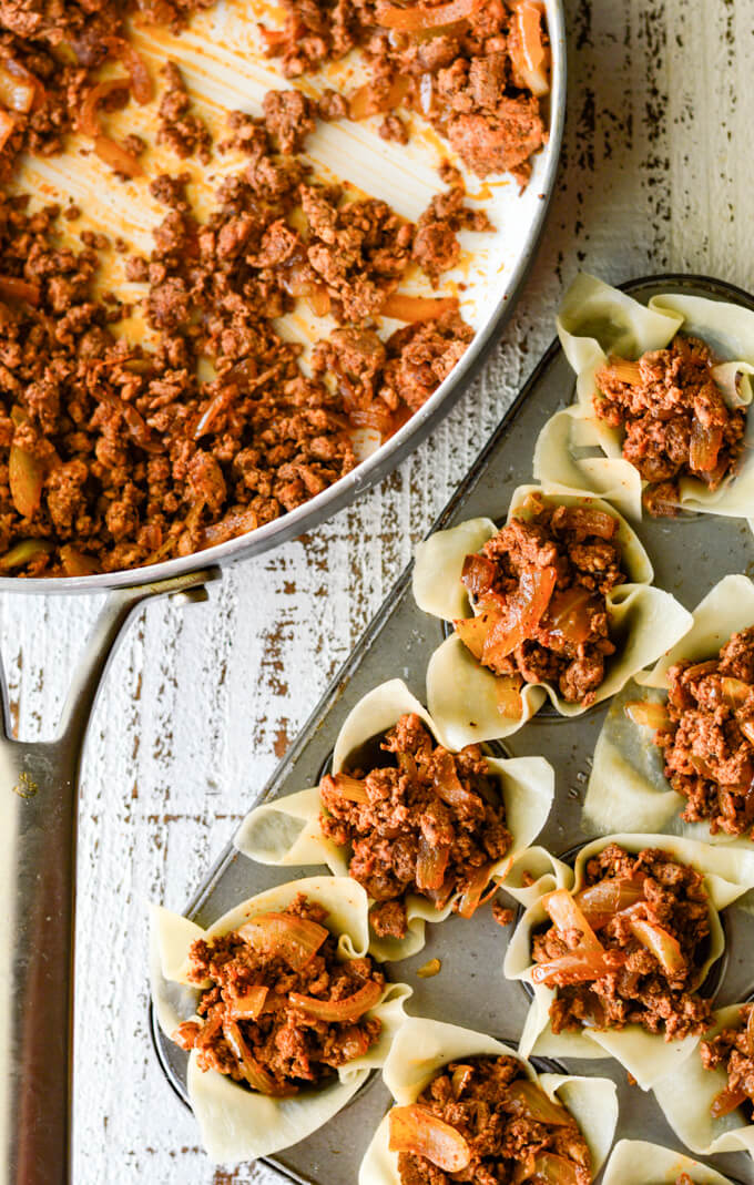 Wontons filled with chorizo sit in a mini muffin tin. A skillet with the meat sits next to the tin.