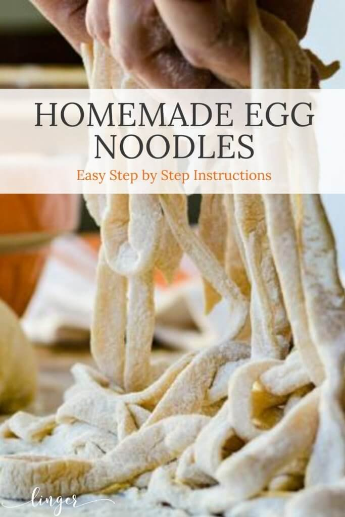 A pile of homemade egg noodles held up by fingers in the shot with an orange mixing bowl in the background with a ball of dough.
