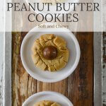 Three peanut butter cookies with chocolate kisses sit on three small white plates that sit on a wooden board.
