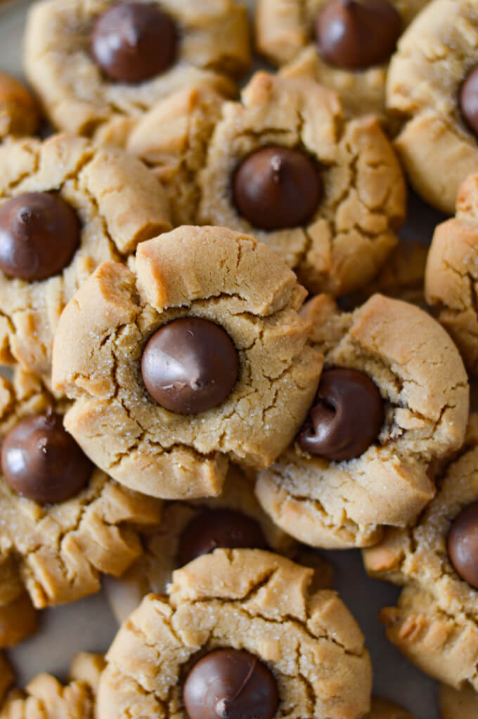 A close-up view of a bunch of baked peanut butter cookies with chocolate kisses.