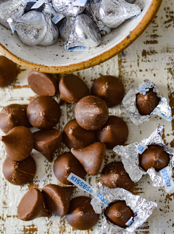 A bunch of unwrapped chocolate kisses sit on a white board next to a bowl of wrapped kisses.