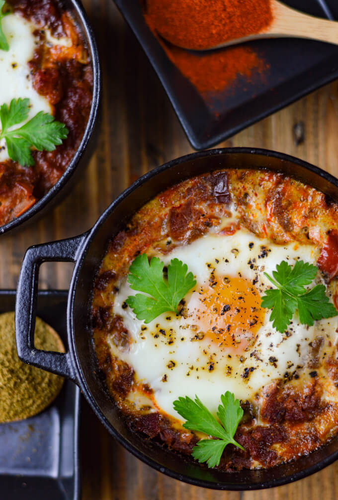 A close-up view of spanish eggs in a mini black cast iron pot with parsley sprinkled o top. Two wooden spoons hold spices next to the Spanish pots.