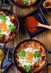 Three pans of spanish eggs cooked in mini cast iron pots with wooden spoons of spices and fresh oregano sit around the pans.
