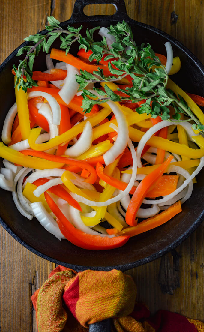 A pan of sliced red, orange and yellow bells peppers with onions in a cast iron pan ready to be sautéed with a sprig of fresh oregano.