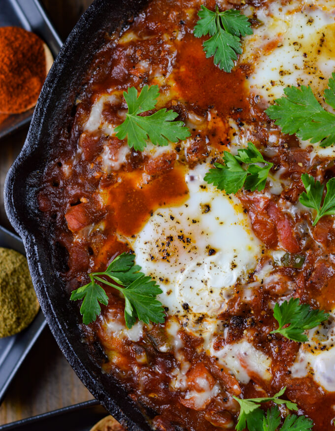 A close-up view of a cast iron skillet of cooked eggs nestled in a spicy tomato sauce. Wooden spoons of spices sits beside the skillet.