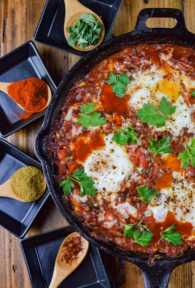A cast iron skillet of cooked eggs nestled in a spicy tomato sauce. Wooden spoons of spices and fresh oregano sits beside the skillet.