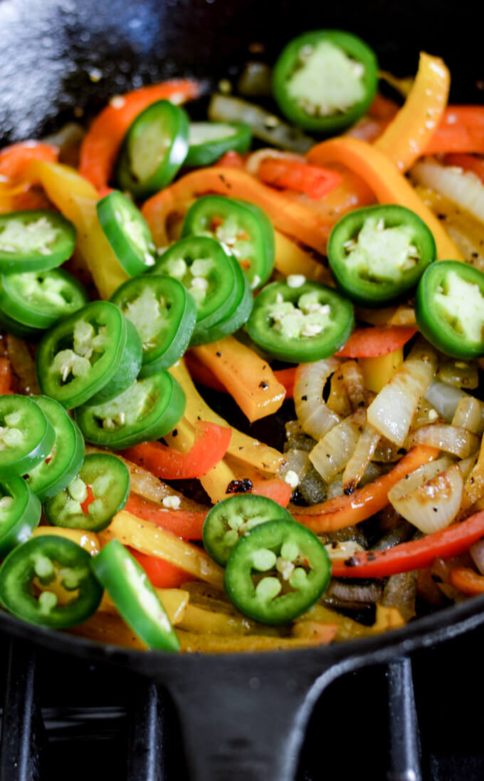 Sautéed red, yellow and orange peppers and onions in a cast iron pan with fresh jalapeño peppers on top.