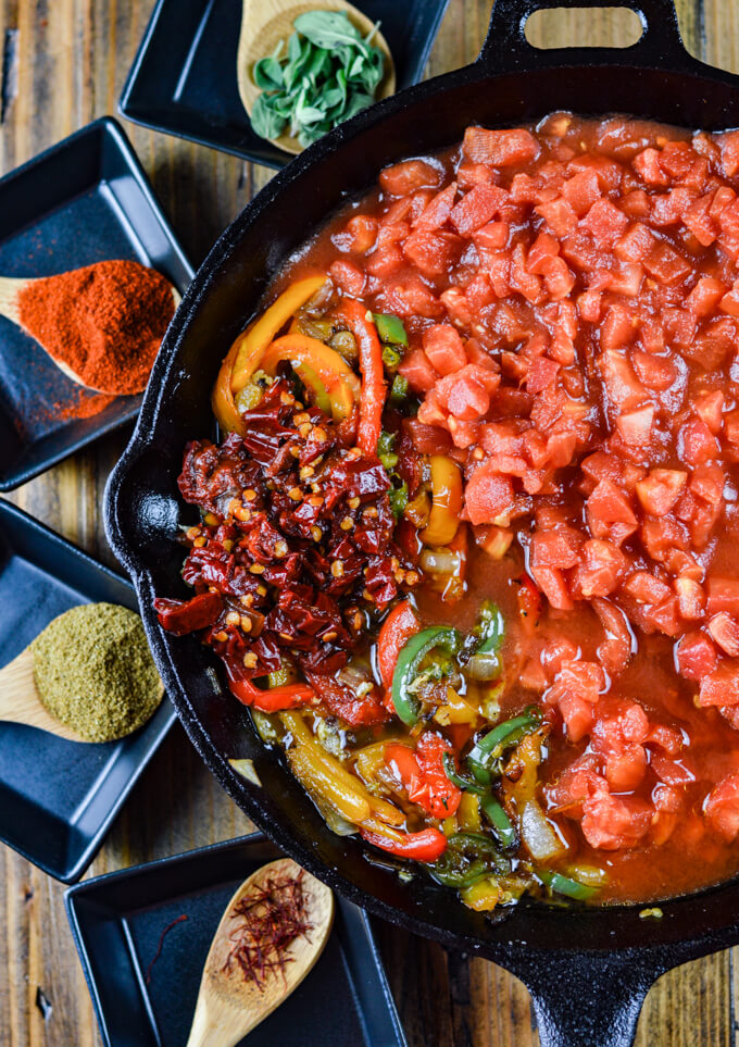 A cast iron pan of diced tomatoes, sautéed bell peppers and onions with jalapeños, and chipotle peppers in adobo sauce with wooden spoons of spices and fresh oregano around the pan.