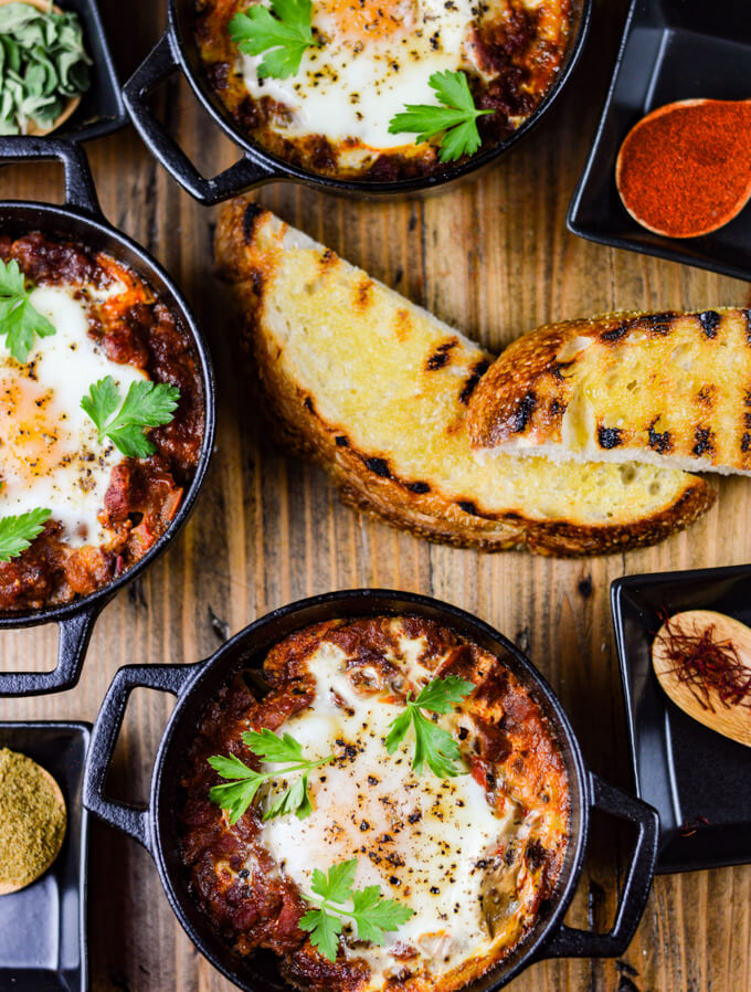 Three pans of spanish eggs cooked in mini cast iron pots with wooden spoons of spices and fresh oregano sit around the pans and two pieces of grilled crusty bread are in the center.