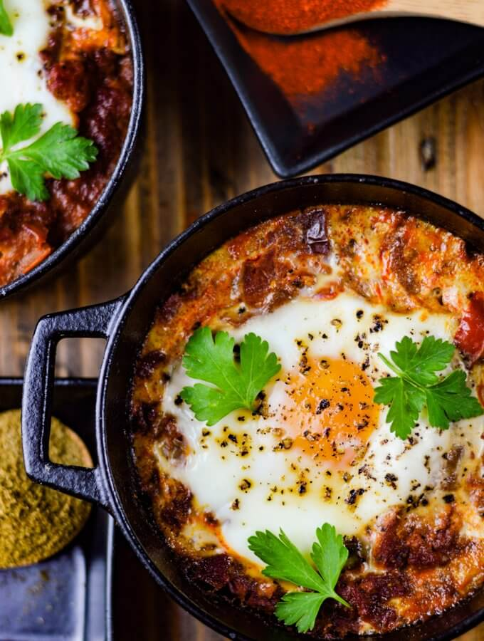 A close-up view of spanish eggs in a mini black cast iron pot with parsley sprinkled on top. Two wooden spoons hold spices next to the Spanish Eggs.