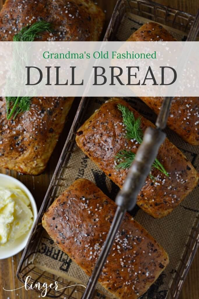 Three mini loafs of baked dill bread in a basket next to a large loaf of the same. A small white bowl of butter sits next to them.