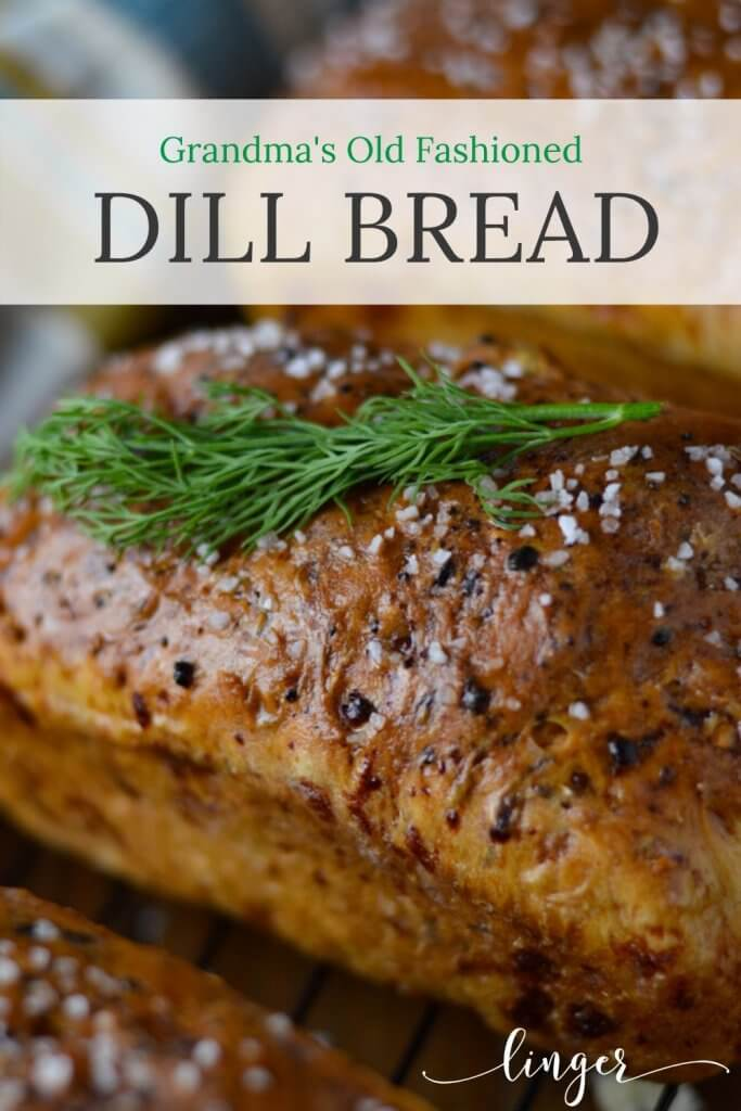 A large loaf of baked dill bread sitting on a wire baking rack with a blue striped napkin in the background.